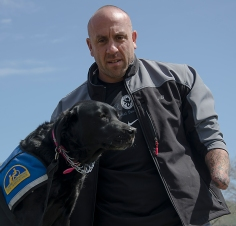 Sam Cila, former U.S. National Guard, lost his left hand after being wounded in Iraq in 2005. He and his facility dog, Gillian, travel the U.S. to motivate and encourage amputees to get involved in sports and recreational activities. Photo by Alexa Gorman