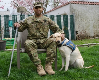 Captain James Van Thach was wounded twice while serving in Iraq. He and his facility dog, Liz, now travel to veteran's centers and homes to speak to soldiers about the effects of PTSD and suicide prevention. Photo by Alexa Gorman